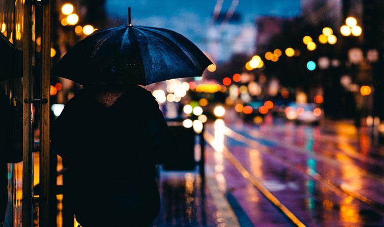 道路沿いで雨に濡れるおとこ
